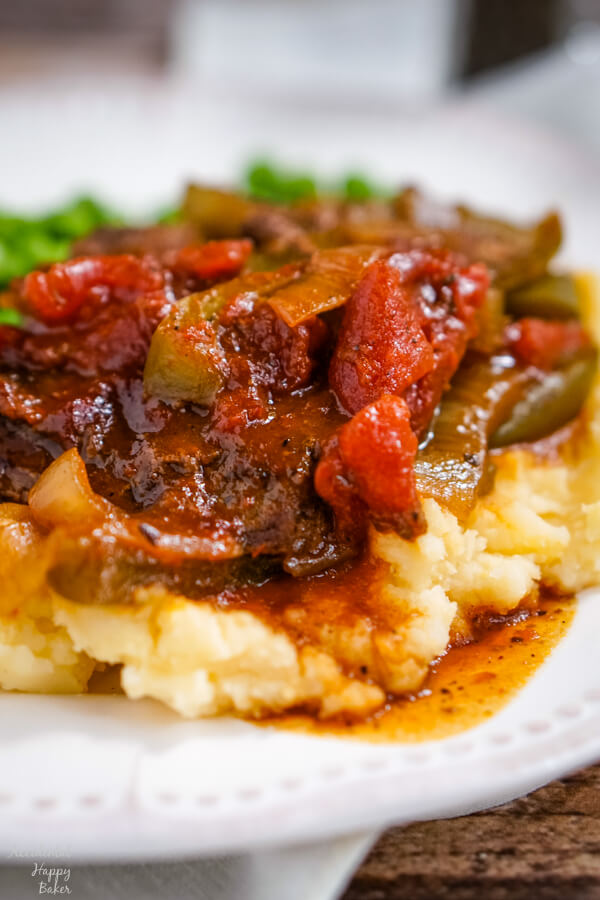 BBQ Swiss Steak with peppers and onions is served up on a pile of cheddar mashed potatoes.