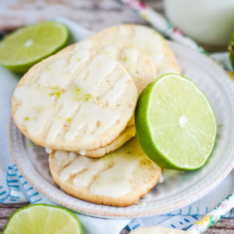 Key Lime Pie Shortbread Cookies stacked on a white plate with slices of lime.