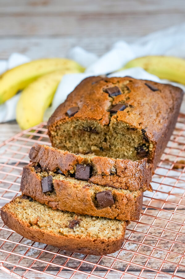 A loaf of chocolate chunk banana bread sliced and sitting on a copper cooling rack.