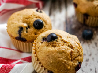 Two blueberry bran muffins on a red and white striped towel.