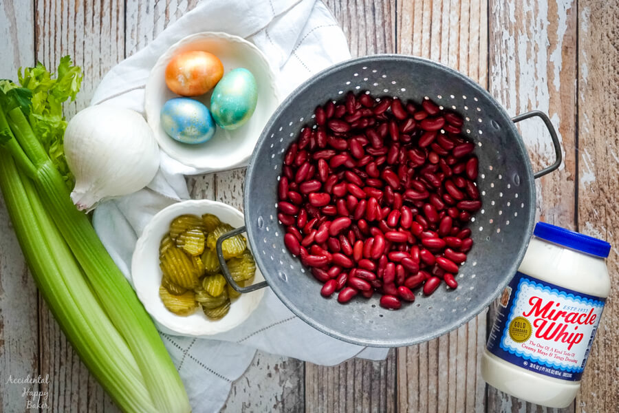 A colander full of drained kidney beans sitting next to celery, onion, pickles, hard boiled eggs and miracle whip.