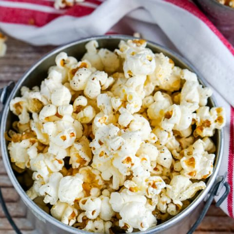 A metal container full of fresh popped Dutch oven popcorn.