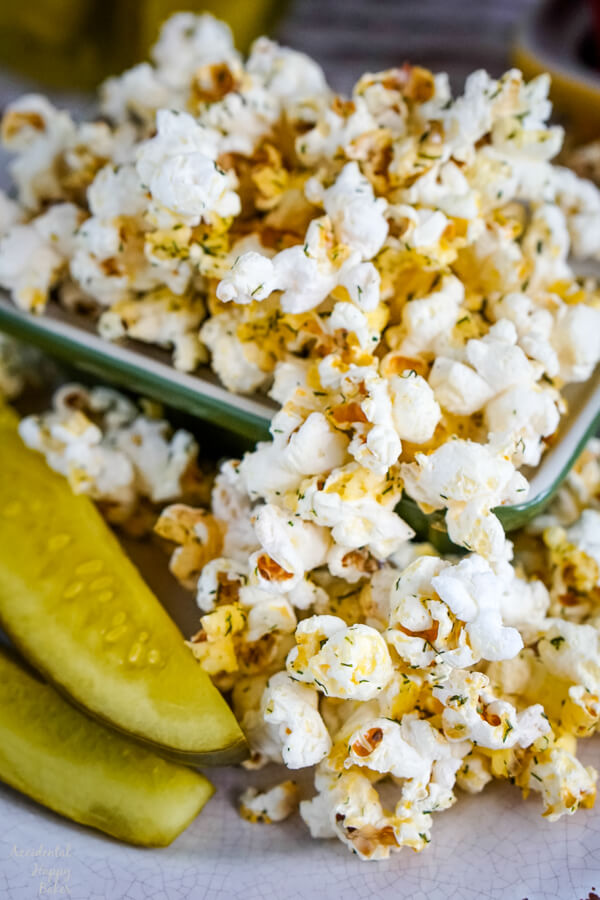 A bowl of dill pickle popcorn next to two dill pickle spears.