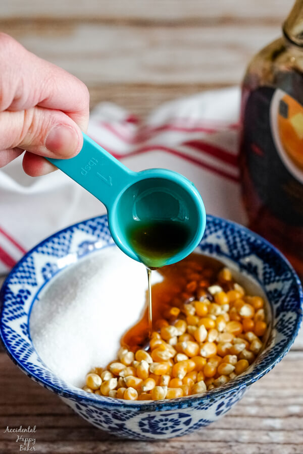 Maple syrup is added to a bowl of popcorn kernels and sugar.