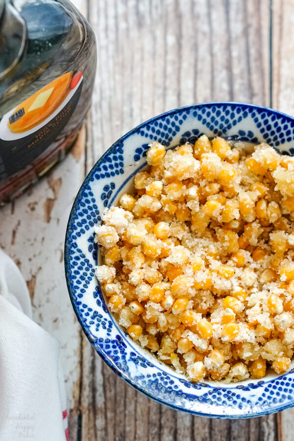 Popcorn kernels are mixed with sugar, and maple syrup before being added to the Dutch oven.
