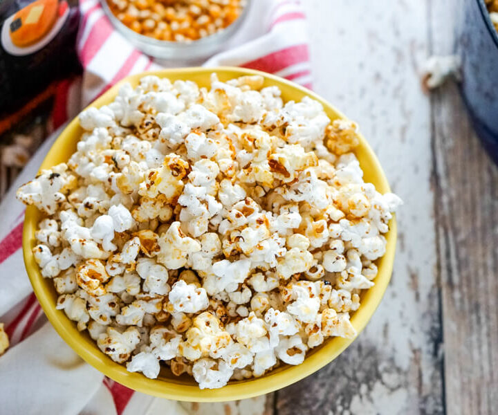 A yellow bowl of kettle corn next to a bottle of maple syrup.