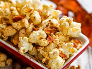 A red bowl full of smoky bacon popcorn.