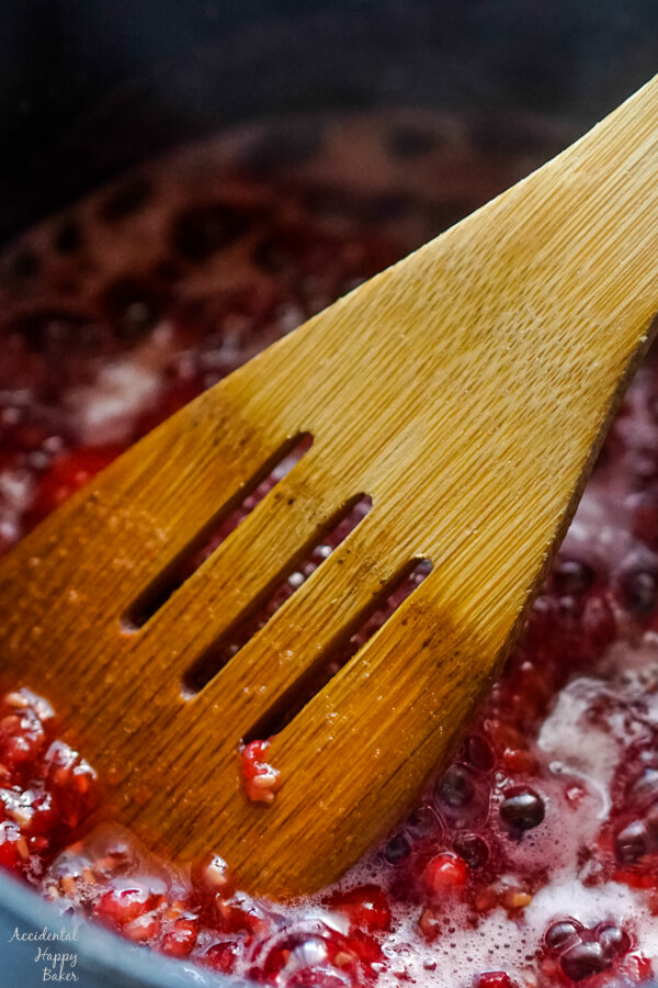 A close up of the cooking raspberries being smashed with a wooden spoon.