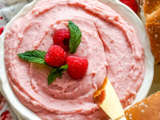 A bowl of raspberry honey butter with a butter knife.