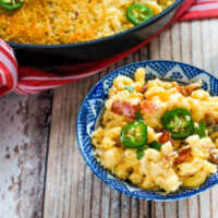 A blue and white bowl full of jalapeno bacon mac and cheese next to a skillet.