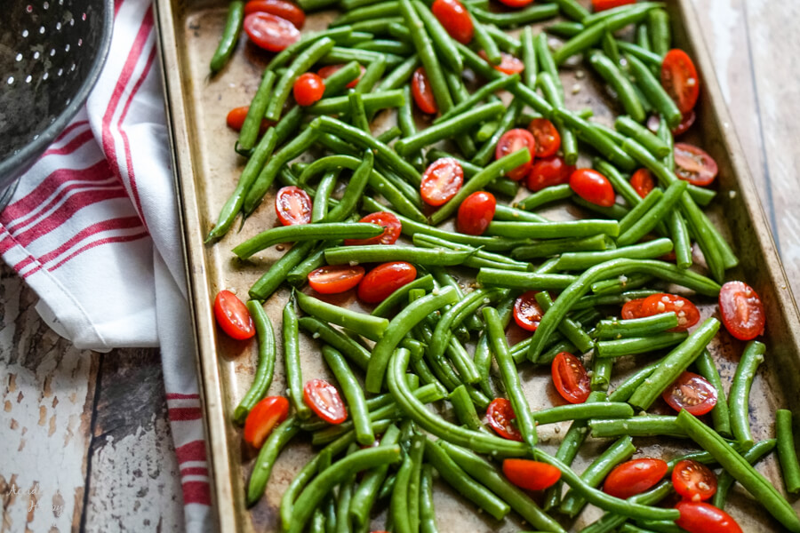 Green beans and tomatoes drizzled with olive oil and garlic on a sheet pan.