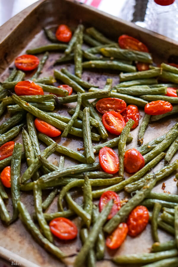 Green beans and cherry tomatoes on a sheet pan just after coming out of the oven.