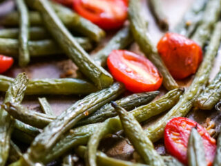 A close up image of a spatula scooping up a serving of roasted green beans and tomatoes.