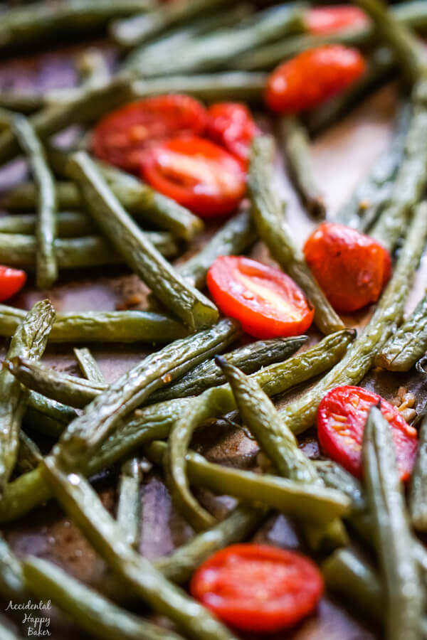 A close up shot of the green beans and tomatoes after they have been roasted in the oven.