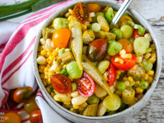 A bowl of Succotash Salad accented with slices of pickled okra.