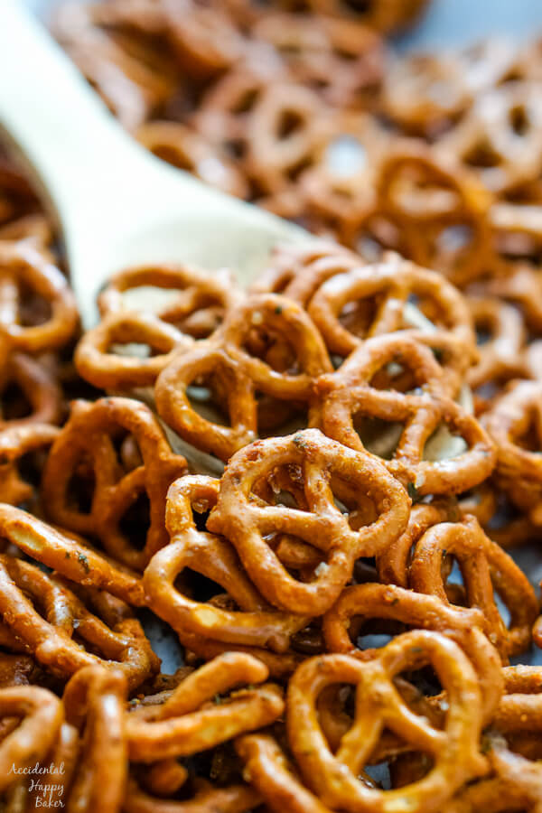 A wooden spoon scooping up some pretzels.