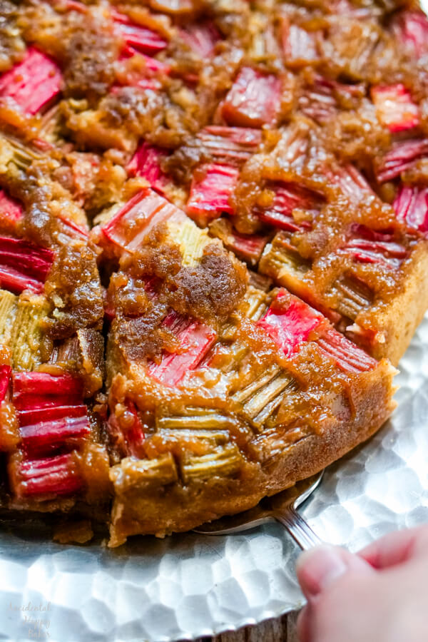 A slice of rhubarb ginger upside down cake being served.