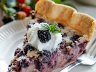 A slice of blackberries and cream pie on a white plate garnished with whipped cream, mint and fresh blackberries.