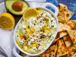 A white serving bowl of lemon feta dip surrounded by pita chips.