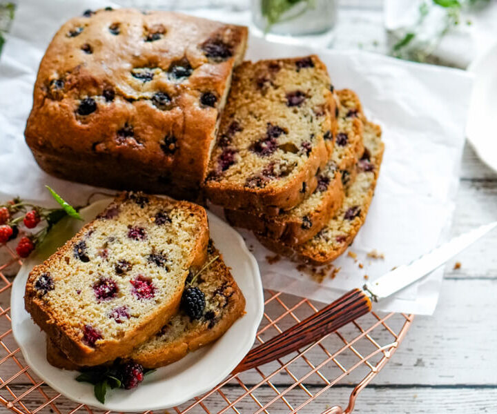 Two slices of blackberry bread on a white plate next to a loaf of sliced blackberry bread.