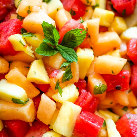 A close up image of watermelon fruit salad that shows the blend of watermelon, cantaloupe, pineapple, and fresh mint.
