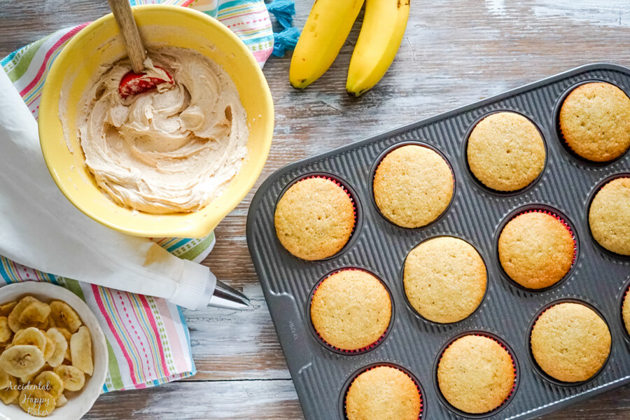 A bowl of peanut butter frosting and a bowl of banana chips next to a pan of cupcakes ready to be frosted and decorated.
