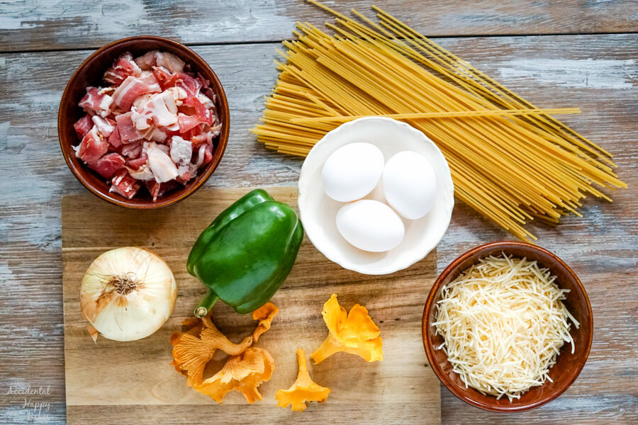 The ingredients for Spaghetti Carbonara. Bacon, pasta, onion, green pepper, eggs, parmesan cheese and mushrooms.
