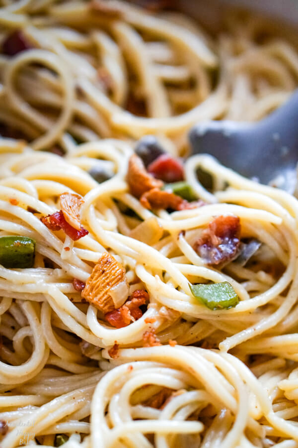 A pan of spaghetti carbonara with a pasta serving scooping out a serving.