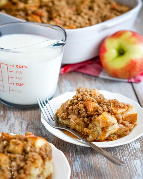 Two servings of Cinnamon Apple French Toast Casserole on white plates with a measuring cup of milk to the side.