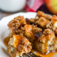 A close up image of a bite of french toast casserole dripping with syrup.