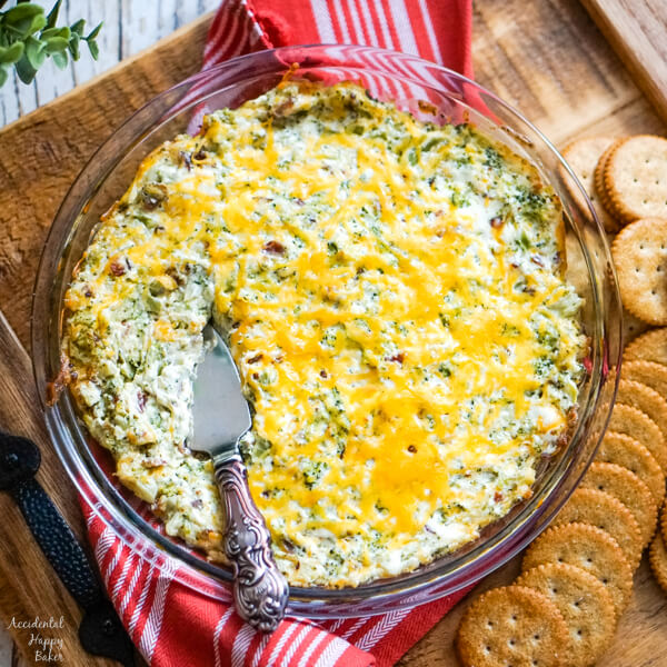A pie plate of cheesy bacon and broccoli dip hot from the oven on a tray with crackers to one side.