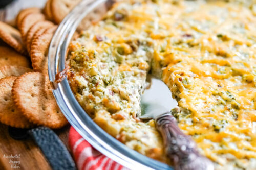A pie plate of cheesy bacon and broccoli dip with a bronze server.