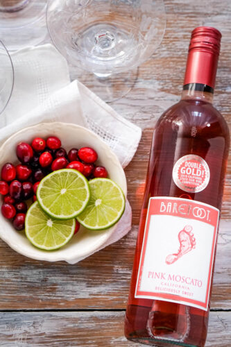 A bottle of pink moscato wine next to a bowl of cranberries and sliced limes.