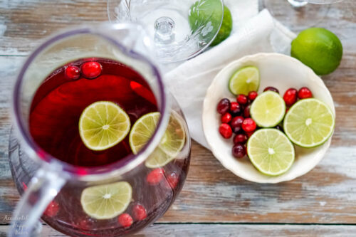 A pitcher of punch with a bowl of sliced limes and cranberries next to it.