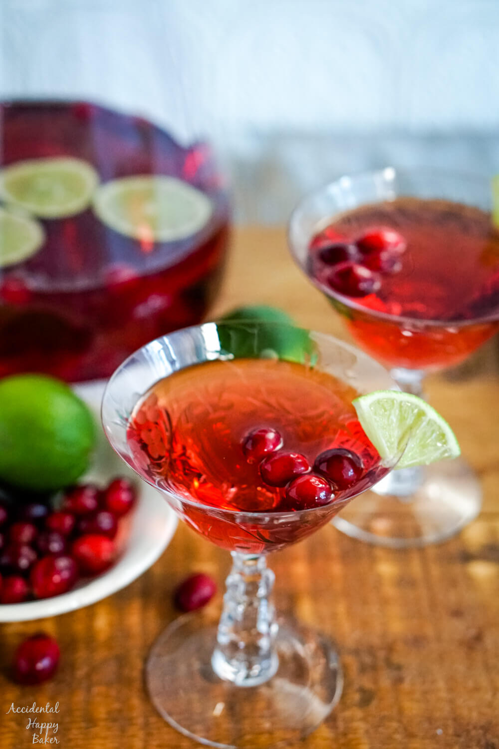 A glass of cranberry moscato punch on a wooden serving tray.