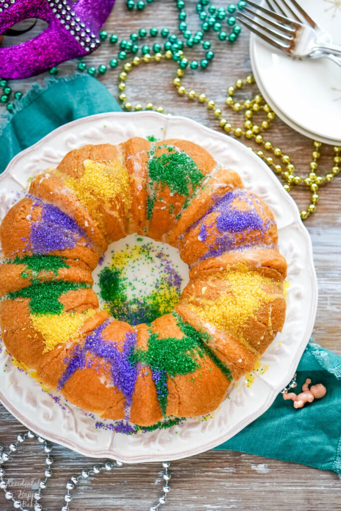 A white plate holding a king cake made from crescent rolls on a table spread with Mardi Gras beads.