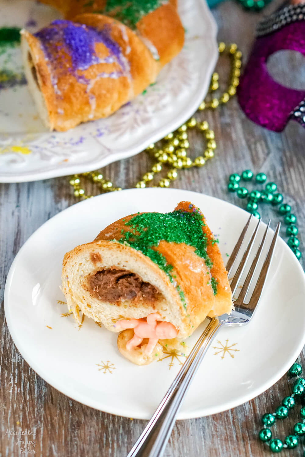 A slice of king cake on a white plate with mardi gras beads in the background.