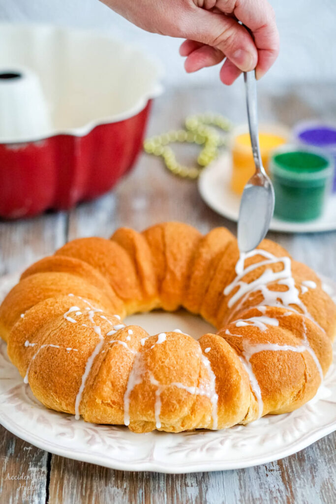 The baked king cake is drizzled with glazed before being decorated with colored sugar.