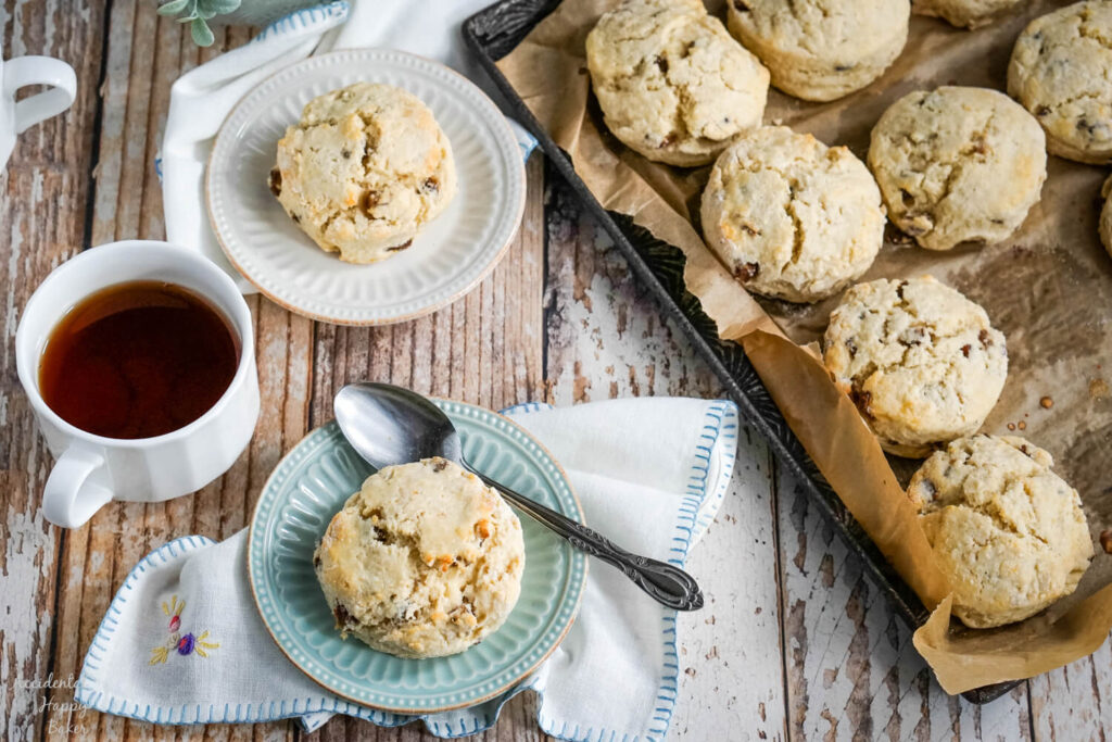Two scones are served on plates next to a tray of date scones.