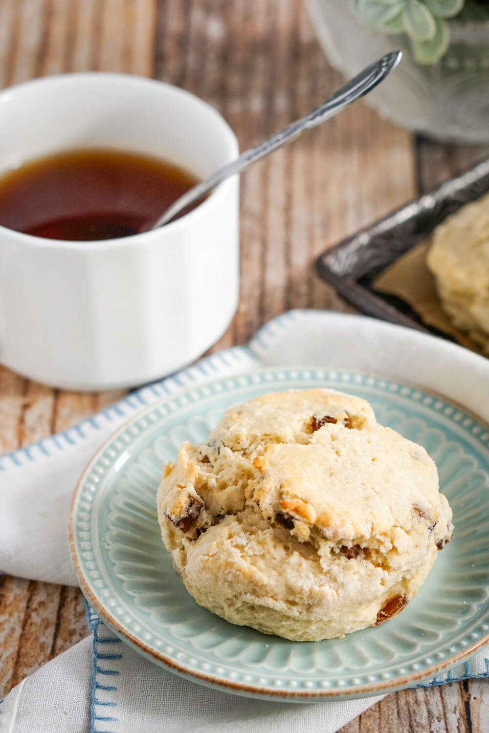 A Date Scone on a blue plate next to a cup of tea.