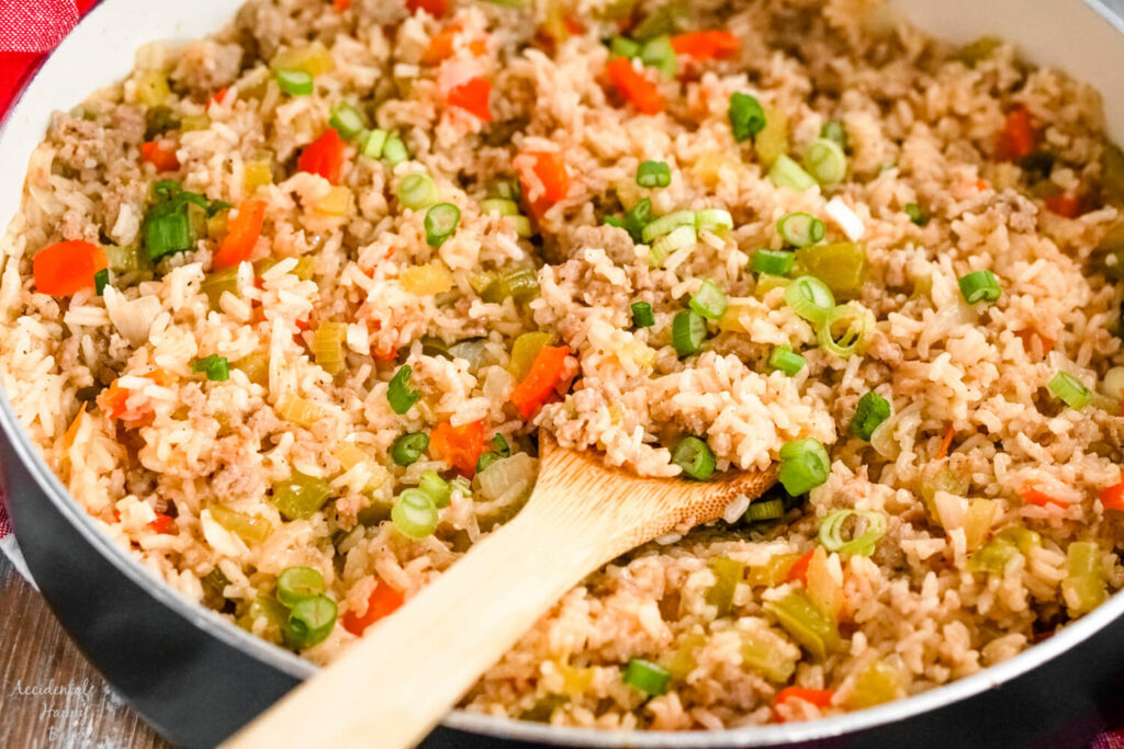 A skillet full of dirty rice with sausage with a wooden spoon holding a scoop of rice.
