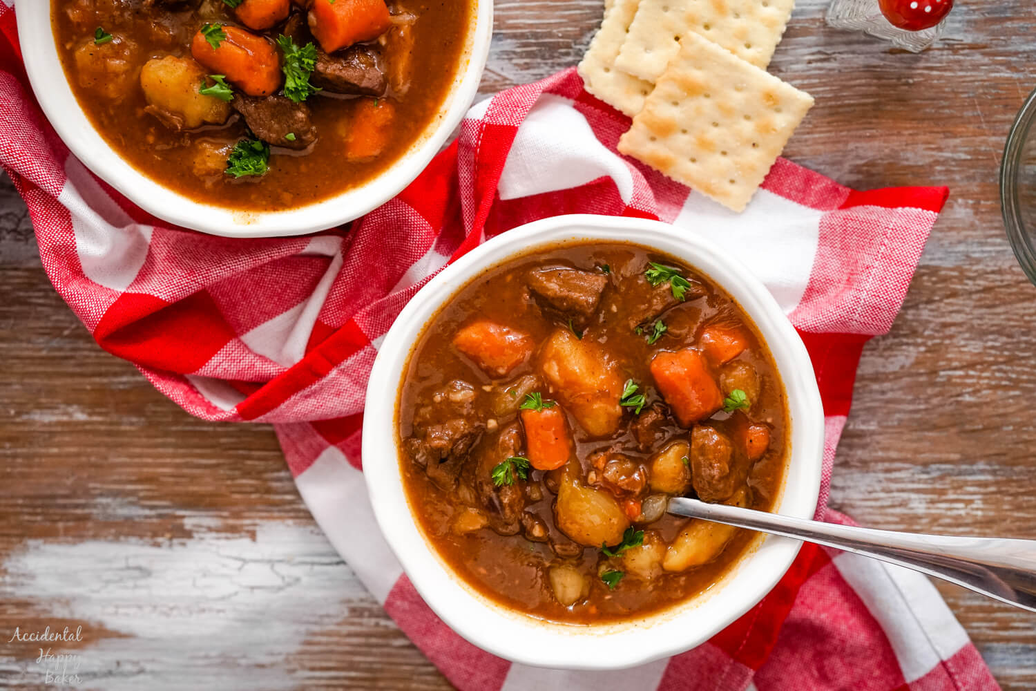 Two bowls of beef stew on a red checkered cloth with saltine crackers.