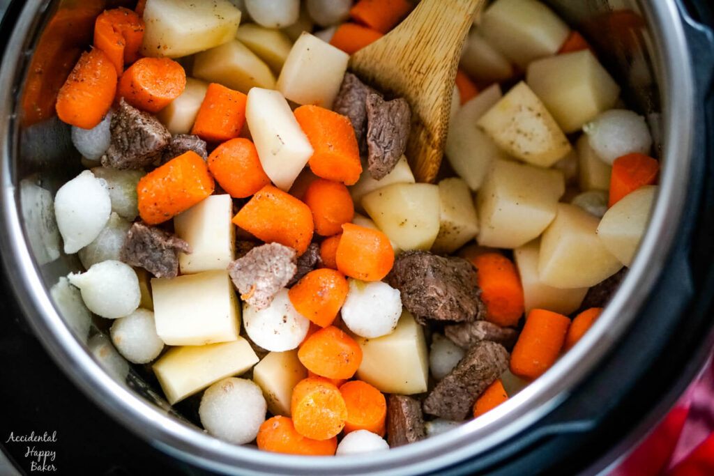 Potatoes, carrots, and pearl onions are added to the instant pot.