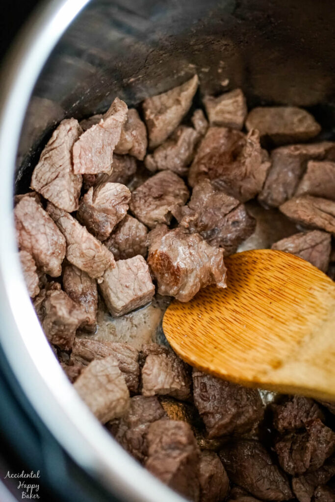 Cubed stew beef is browned in oil in the instant pot.