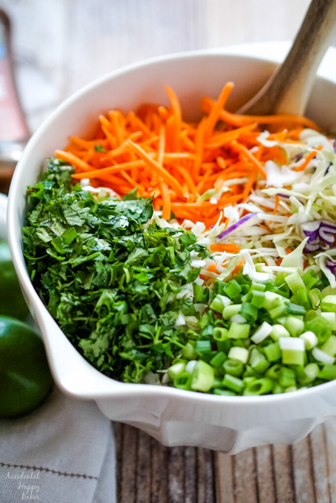 A bowl full of coleslaw mix, shredded carrots, chopped cilantro and green onions.