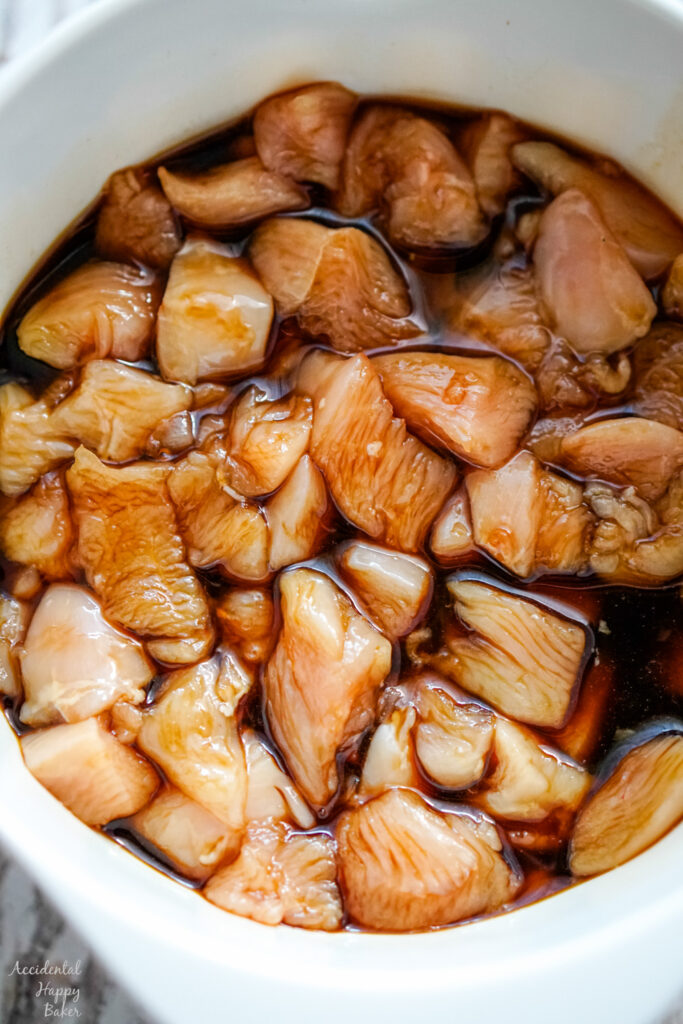 A bowl of chopped chicken soaking in the marinade.