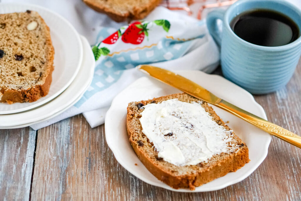 A thick slice of tea loaf slathered with butter next to a cup of tea.