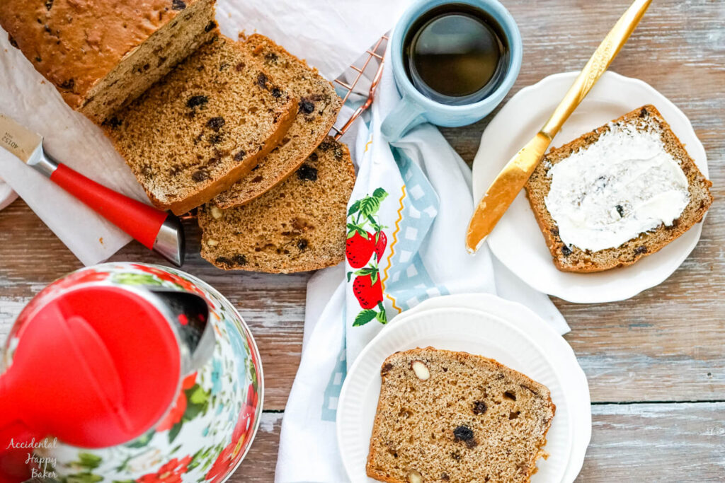 A loaf of sliced Bara brith bread next to a cup of tea, a kettle, and slices of Welsh tea bread.