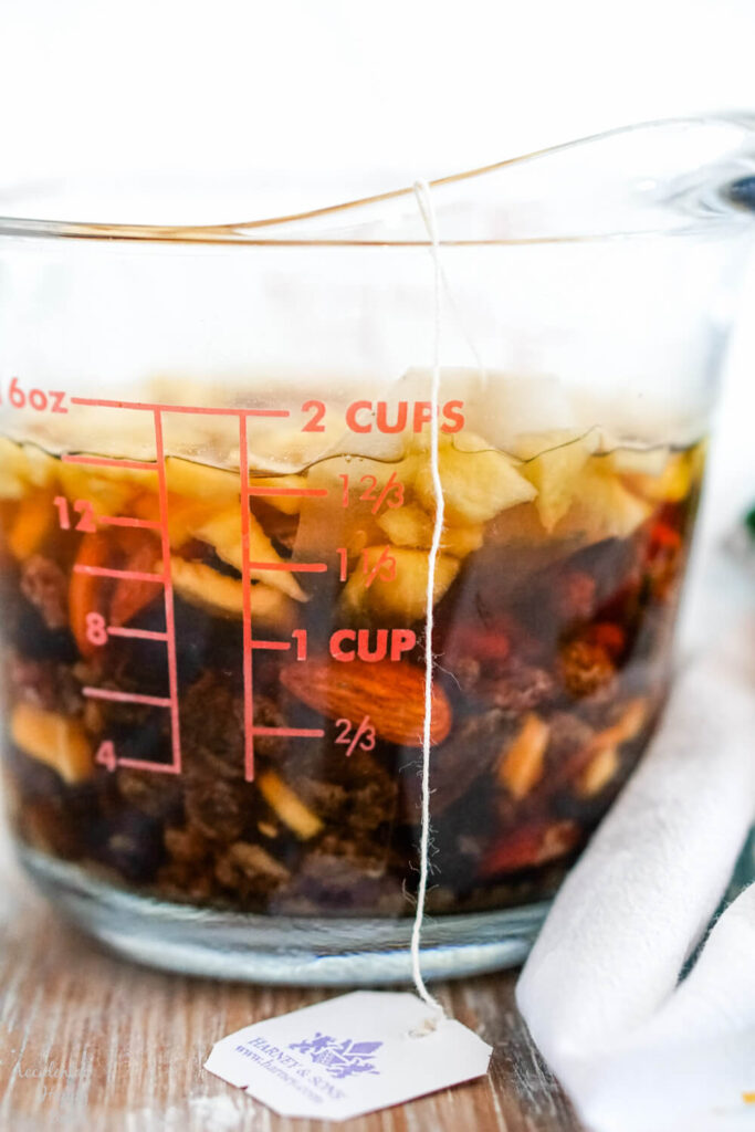 The dried fruit and tea steep together in the boiling water.