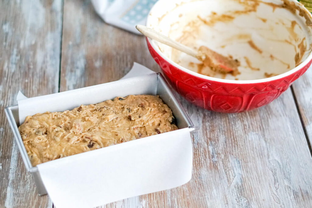 The bread batter is spread in a parchment lined bread loaf pan.